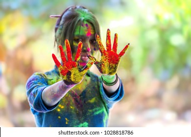 Indian young girl showing colourful palm and celebrating holi festival