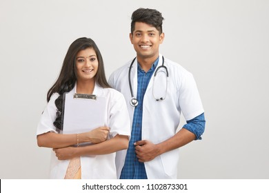 Indian young male and female doctor with note pad