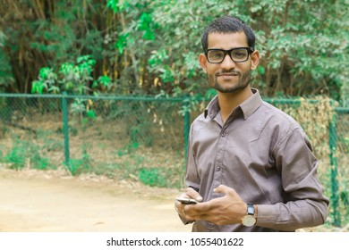 indian young man with his smartphone in thenpark