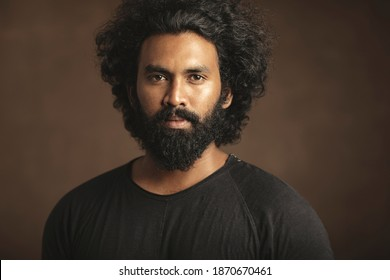 Indian young man with long hair and beard in studio shot.