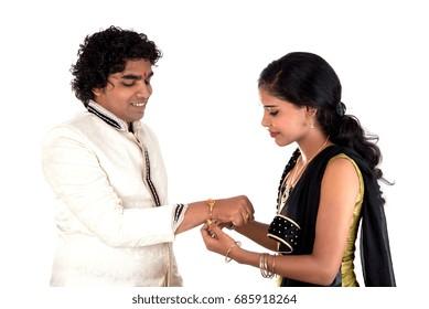 Indian young sister tying rakhi on brother's wrist, a tradition on Raksha Bandhan festival