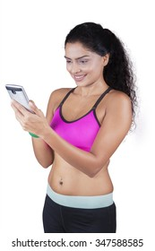 Indian young woman wearing sportswear and holding smartphone with exercise app, isolated on white