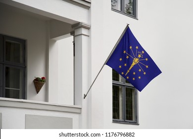 Indiana flag. Indiana state flag hanging on a pole in front of the house. State flag waving on a home displaying on a pole on a front door of a building. Flag raised at a full staff.