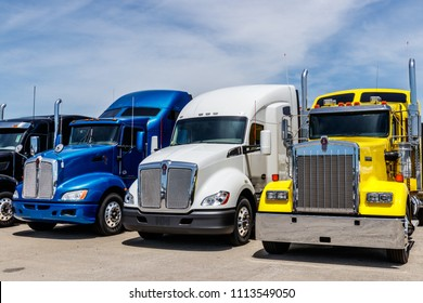 Indianapolis - Circa June 2018: Colorful Semi Tractor Trailer Trucks Lined up for Sale II