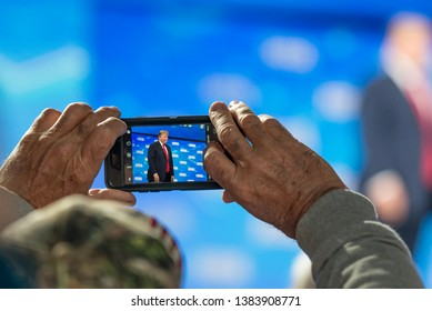 Indianapolis, Indiana / USA - April 26 2019: Man wearing camo American Flag hat taking cell phone picture of President Donald Trump at NRA Meetings Convention Leadership Forum