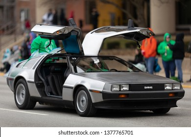 Indianapolis, Indiana, USA - March 15, 2019: St. Patrick's Day Parade, A DMC Delorean collectors car, with it is gull wing doors open, going down the road during the parade