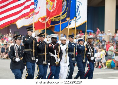 Indianapolis, Indiana, USA - May 26, 2018,  Members of the US Military carrying the American flag marching down the street during the Indy 500 Parade