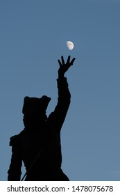 Indianapolis Monument Circle bronze statue of Colonial General George Rodgers Clark with waxing moon in the background.  He became the highest-ranking American military officer on the northwestern fro