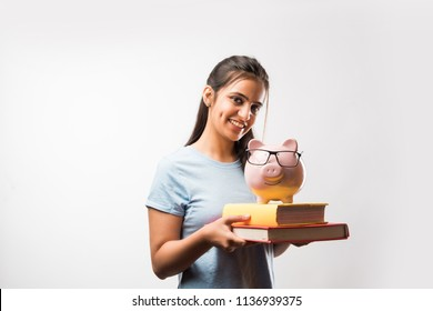Indian/asian attractive female student holding piggy bank over white background with or without books, selective focus