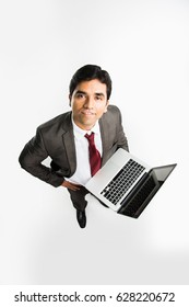 indian/asian businessman holding laptop over white background and looking upward towards camera, a view from top also known as bird's eye view