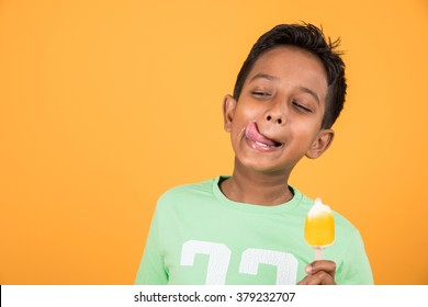 Indian/Asian cute little boy eating Ice cream in cone or mango bar/candy. Isolated over colourful background