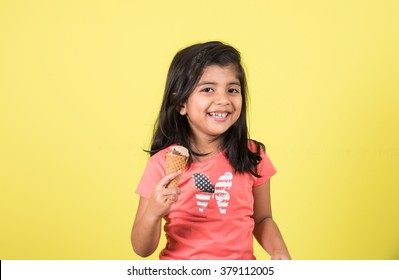 Indian/Asian cute little girl eating Ice cream in cone or mango bar/candy. Isolated over colourful background