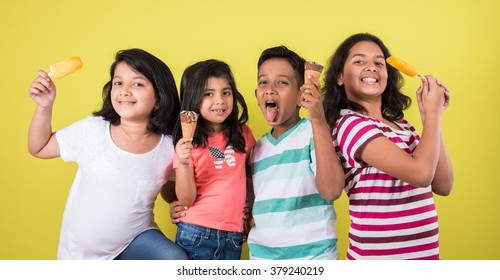 Indian/Asian cute little kids eating Ice cream/mango bar or candy. Isolated over colourful background