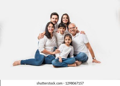 indian/asian family sitting over white background. senior and young couple with kids wearing white top and blue jeans. selective focus