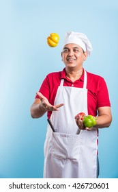 Indian/Asian handsome male chef in uniform, holding fresh vegetable, standing isolated over blue background