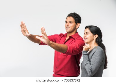 Indian/Asian Handsome Man setting Frame with both hands and beautiful wife watching curiously, standing isolated over white background