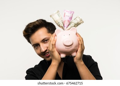 Indian/Asian Handsome Young Man with Piggy Bank Or Money Box with different expressions, standing isolated over white background