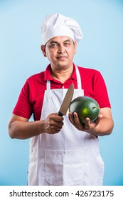 Indian/asian male chef holding knife in one hand and water melon fruit in other hand, isolated over blue background