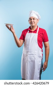 Indian/Asian male chef in uniform presenting an empty plate and smiling, standing isolated over plain blue background