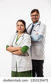 Indian/asian male and female doctor / medical professional in uniform with hands folded. standing isolated over white background