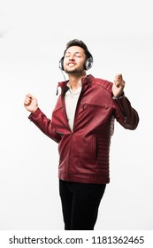 Indian/asian Man with headphones while wearing leather jacket and dancing. isolated over white background