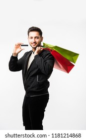 Indian/asian man showing his shopping bags and credit or debit card while standing over white background