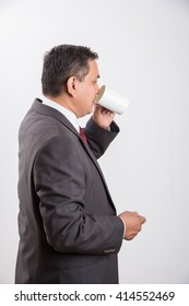 Indian/Asian mid aged handsome businessman in black suit having a sip of coffee/Tea while standing isolated over white background