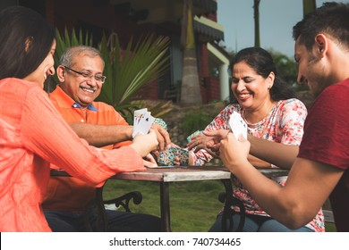 Indian/asian MODERN family playing cards and having fun while sitting in lawn, outdoor