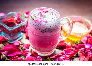 Indian/Asian popular summer drink i.e. Gulab Shake or Rose shake consisting of milk,rose syrup,sugar and honey with sabja seeds or sweet basil seeds in a transparent glass,with all ingredients.
