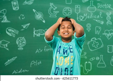 indian/asian school boy pulling hair in sadness or distress because of study pressure or competition, standing isolated over green chalkboard background