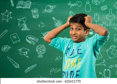 indian/asian school kid or boy pulling hair in sadness or distress because of study pressure or competition, standing isolated over green chalkboard background