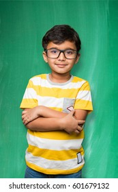 indian/asian school kid with clear eye glasses or spectacles, standing over green chalkboard background