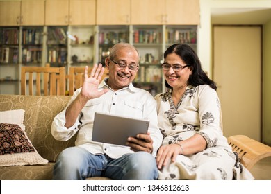 Indian/asian Senior couple video chatting on tablet/computer while sitting at couch or in garden at home, selective focus