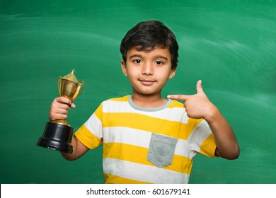 indian/asian small school kid holding trophy or winning cup,
