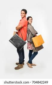 ac3478cdd7 Indian/Asian smart couple shopping, holding colourful Bags, isolated over  white background