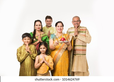 Indian/Asian smart family welcoming Lord Ganesha Idol on Ganesh Festival with Pooja Thali and sweets. standing isolated over white background
