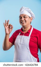 Indian/Asian smiling indian male chef cook showing ok sign isolated on blue or white background
