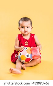 Indian/Asian Toddler/Infant or baby playing with sipper or toys blocks while lying or sitting isolated over bright or colourful background