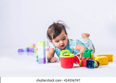 Indian/Asian Toddler/Infant or baby playing with toys or blocks while lying or sitting isolated over bright or colourful background