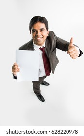 indian/asian young businessman holding a blank white paper and showing success sign or thumbs up, a bird's eye view from top showing perspective view