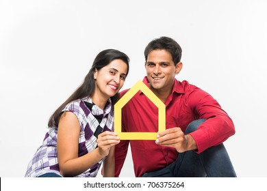 Indian/Asian young couple Buying / Dreaming for Home OR Real Estate concept, holding 3D colourful Paper model of house. Isolated over white background