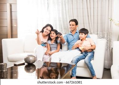 Indian/asian young Family Watching TV Together while sitting at sofa, selective focus