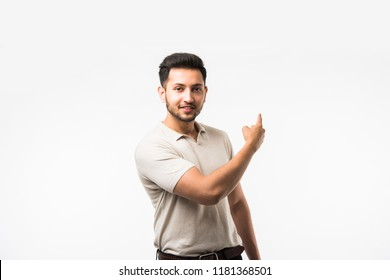 Indian/asian young man pointing something while standing isolated over white background with copy space