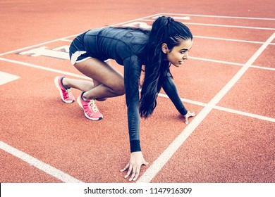 Indian/Mexican Woman in crouching starting position on running track. Wearing running shorts, black long sleeve top, pink running shoes. Long black hair in pony tail. Ethnic, Multicultural, Inclusive.