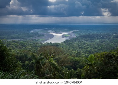Indichuris viewpoint located in the Amazon Rainforest of Ecuador. The confluence of the Pastaza and Puyo rivers, a dense vegetation and a sky covered with large clouds can be appreciated.