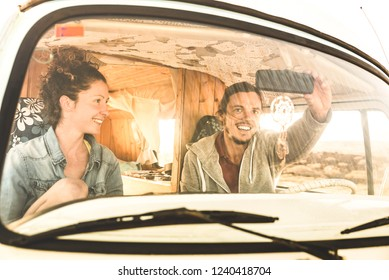 Indie couple ready for roadtrip on oldtimer mini van transport - Travel lifestyle concept with young hippie people having fun traveling on minivan adventure trip - Warm bright filter