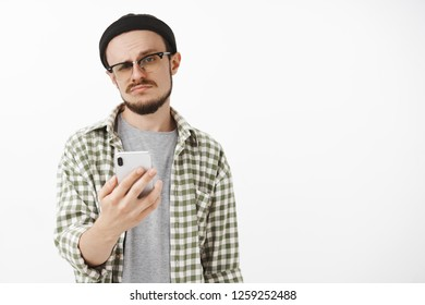 Indifferent male young snob in glasses and beanie with beard holding smartphone smirking and staring at camera careless and unimpressed receiving offer via messages and being dissatisfied