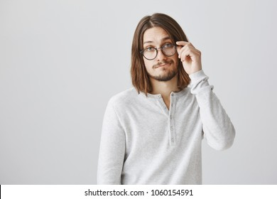 Indifferent smart snob did not care about nightlife. Portrait of attractive european guy in glasses standing with gloomy smile, being focused and uninterested in discussion, getting back to work