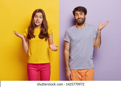 Indifferent unbothered woman and man spread hands sideways, have no idea, dressed in casual outfit, pose against different color background. Confused questioned couple with clueless expression indoor
