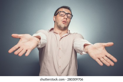 Indigence. I have nothing, young man with outstretched arms over dark gray background. Funny guy or businessman showing his palm - empty hands. Studio shot